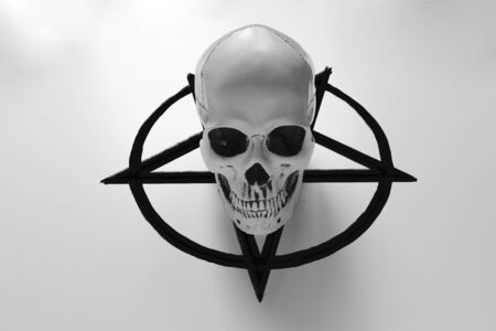 White human skull on top of black pentagram on white background