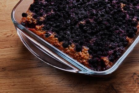 Baked oatmeal with blueberries in a pan on a wooden table Stock Photo
