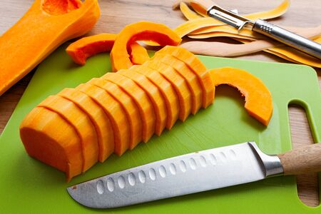 Sliced bright orange butternut squash on green cutting board,  knife lying on the side
