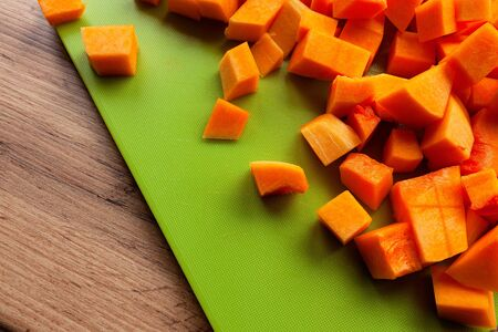 Vibrant, bright orange butternut squash, cut in cubes on green cutting board