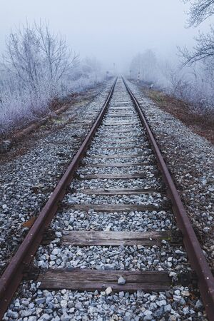 Railroad tracks leading into the unknown, surrounded by winter scenery