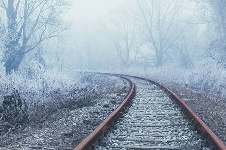 Old and rusty railroad tracks curving into the distance, winter landscape all around