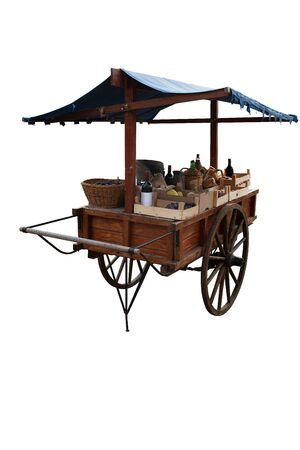 Old wooden cart with many trinkets, bottles and staff for selling on the market, white background
