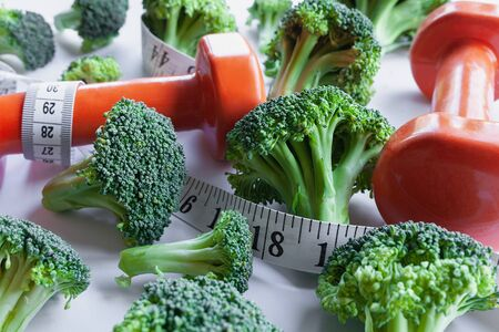 Fresh broccoli florets intertwined with measuring tape and pair of orange dumbbells
