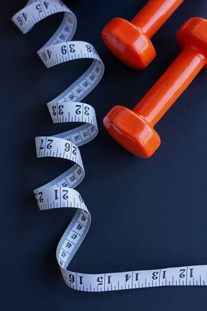 Two orange dumbbells and tape measure on dark