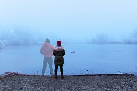 Lonely woman in winter coat standing by the lake in winter, with transparent man figure standing next to her
