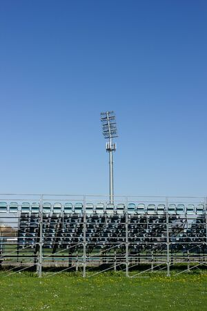 Empty bleachers outside on a soccer field, blue sky and green grass