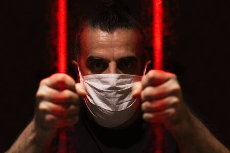 Man with white medical mask standing in the dark, holding red bars made of viruses with his bare hands, locked away in dark, in isolation and quarantine Foto de archivo