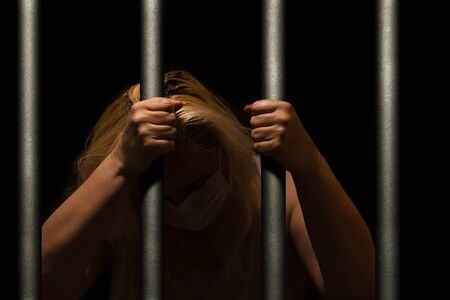 Blonde woman behind the bars, in dark, crying and hiding her face, holding bars with her hands