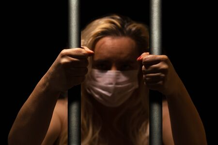 Blonde woman behind the bars wearing white medical mask, holding bars with her hand, alone in dark