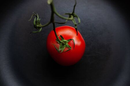 Red tomato with green stem on a black background