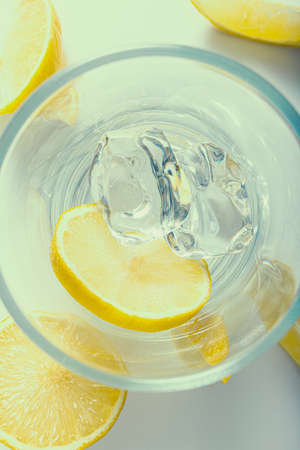 Top view of glass filled with lemon slices and ice cubes, summer cold drink, with slices of lemon around it