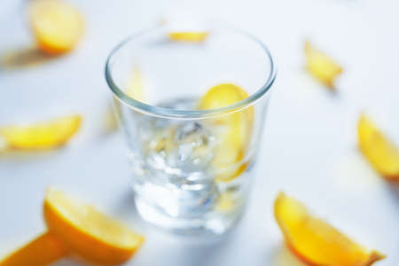 Out of focus glass filled with ice cubes and lemon slices, surrounded with slices of lemon
