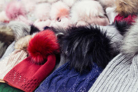 Rows of colorful wool hats with fluffy pom poms