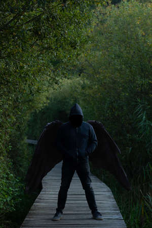 Man with black wings in jeans and dark hoodie, face hidden in shadow, standing menacing on wooden footpath in forest, fallen angel concept