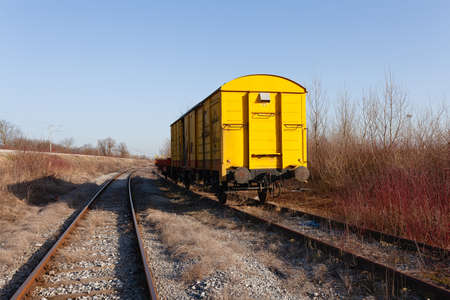 Abandoned yellow train wagon, weathered and rusty, on an old train tracks