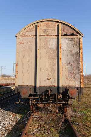 Old abandoned weathered and rusty train cargo wagon on an old train tracks