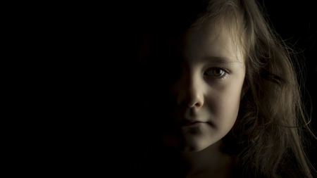Portrait of young girl in studio on black background with copy space Stock Photo