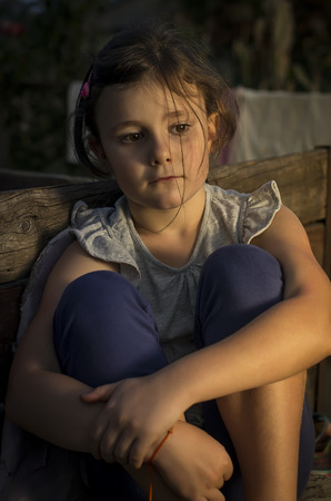 dejected: Seven years old girl sitting sad in a chair in countryside in an evening light.