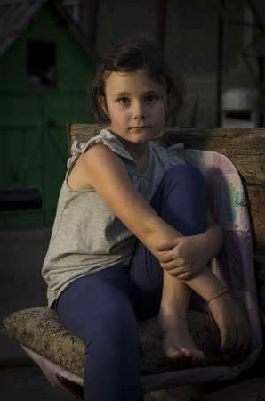 mournful: Seven years old girl sitting sad in a chair in countryside in an evening light.