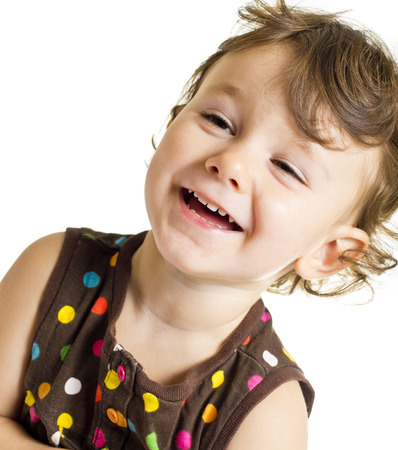 Three years old smiling little girl in brown polka-dot dress.