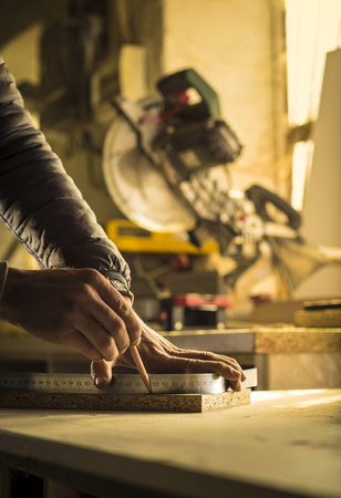 class maintenance: Man doing some carpentry work in a workshop.