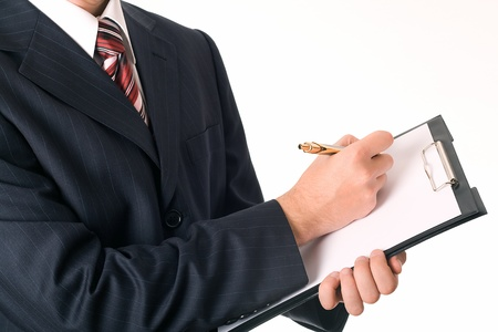 business man in dark suit writting on clipboard photo