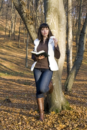 girl reading in autumn forest photo