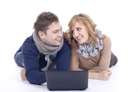young couple lying on the floor while using a laptop  photo