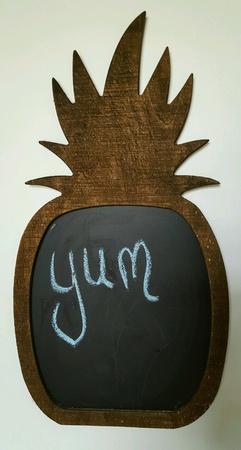 The word yum written in blue chalk on pineapple shaped blackboard. Stock Photo
