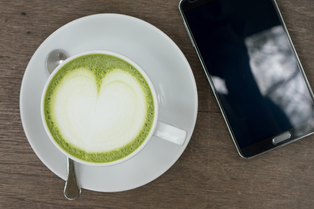 Green tea latte on wood background with the blank screen smartphone Stock Photo