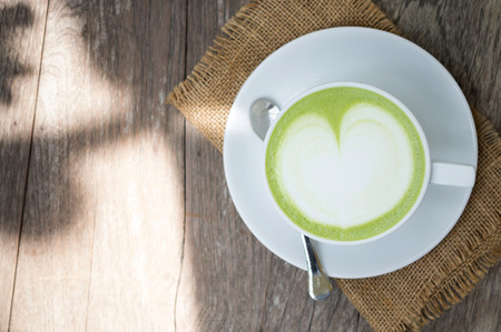 A cup of green tea latte on wood table Stock Photo