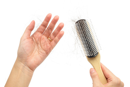 Hair loss in woman hands and bruch, on white background Stock Photo
