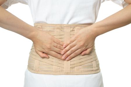 Una donna indossa la cintura di supporto per la schiena isolata su sfondo bianco Archivio Fotografico
