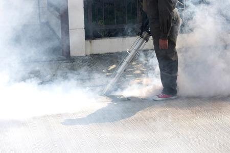 Man using smoke machine for pest control 版權商用圖片