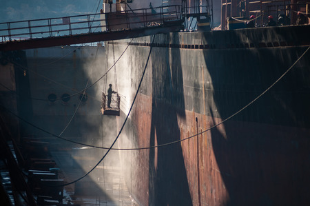 Shipyard worker power washing a ship on dry dock
