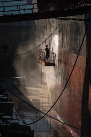 old man on a physical pressure: Shipyard worker power washing a ship on dry dock.