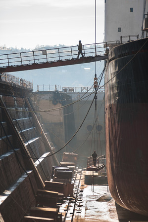 old man on a physical pressure: Shipyard worker on dry dock. Stock Photo