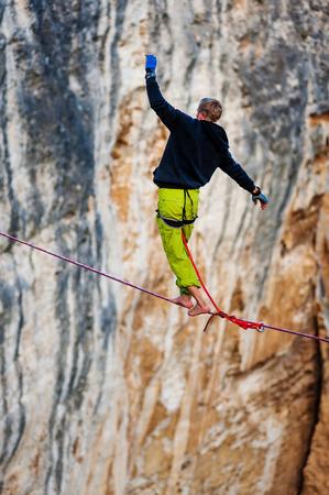 slack: Highline walker over the rock.