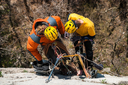 rappelling: Team of climbers rappelling the cliff.