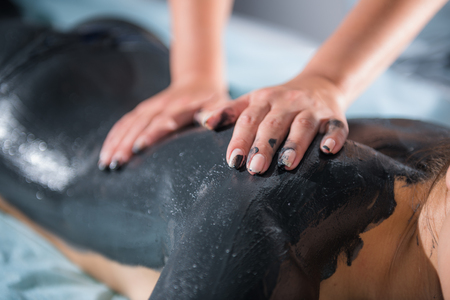 Mud massage with woman hands on body.