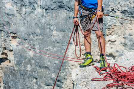 belaying: Human legs on cliff with red rope.