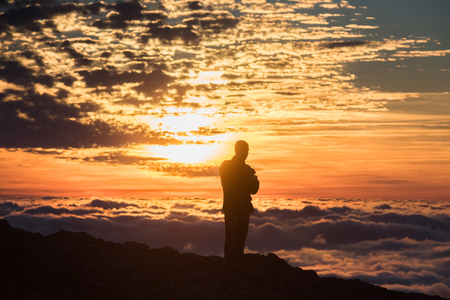 abseil: Young man on a background of a sunset above the clouds in the mountains Stock Photo