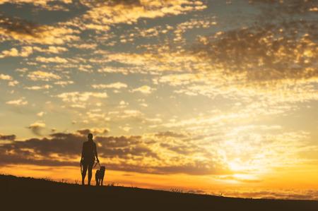 Girl with a dog at beautiful sunset. Zdjęcie Seryjne