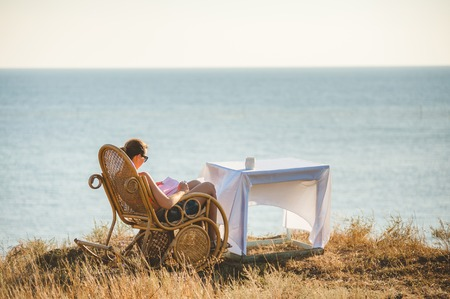 Girl reading a book in the chair against the backdrop of the sea. Stock Photo
