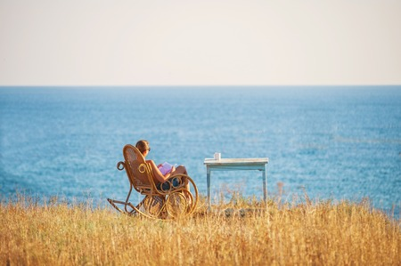 Girl reading a book in the chair against the backdrop of the sea. Zdjęcie Seryjne