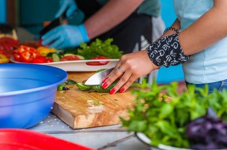 Women's hands cut fresh vegetables with a sharp knife.