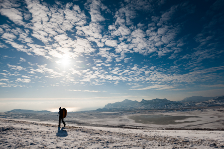 A man with a backpack goes on snow with mountains and the sea on background.