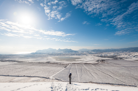Girl on the snowy slope with mountains and the sea on background.