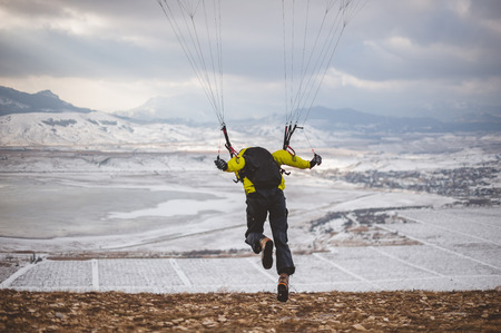 Man takes off with the speedglider from the mountain.